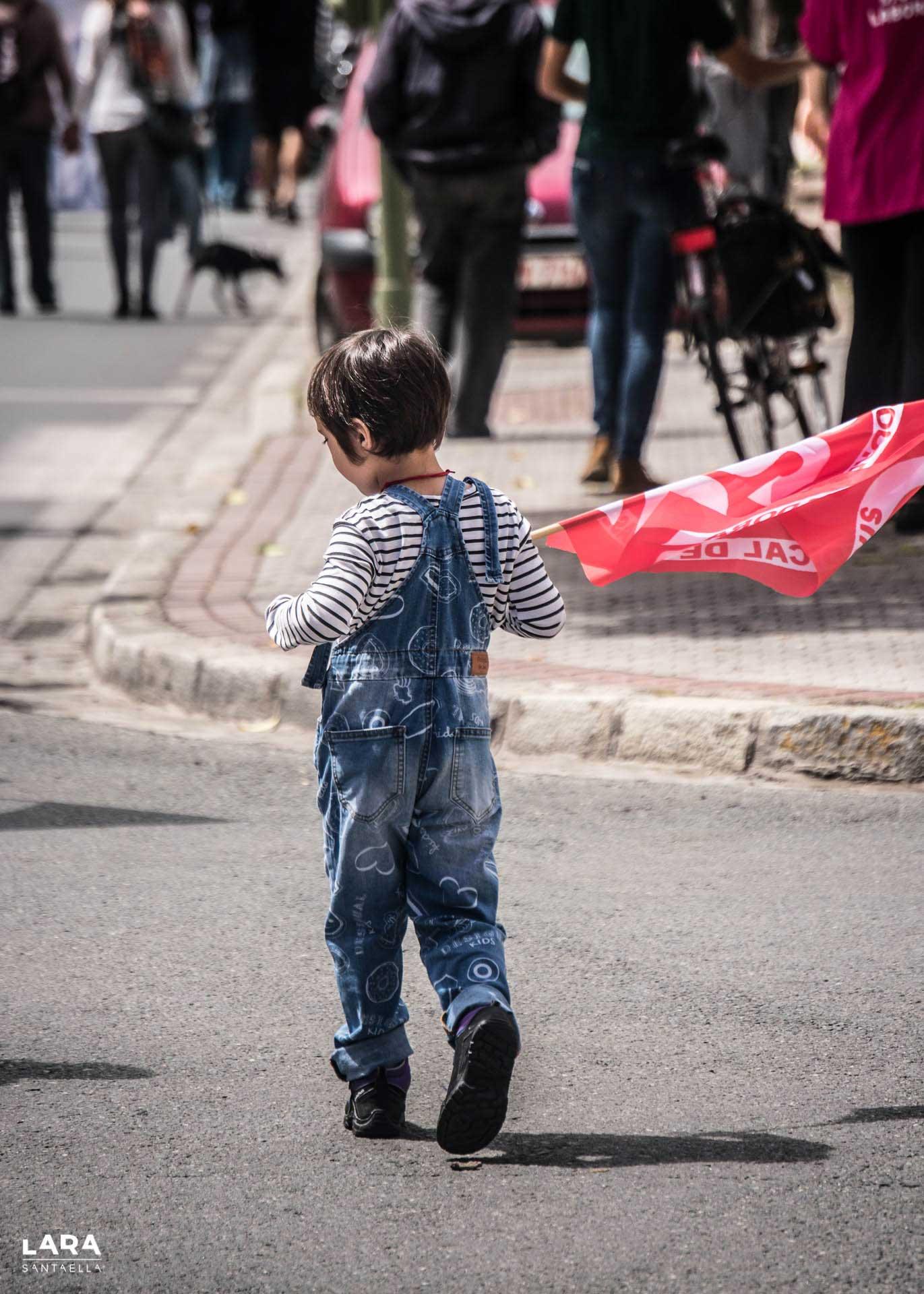 Se ve una niña pequeña caminando de espaldas, con una bandera de un sindicato de trabajadores al hombro.