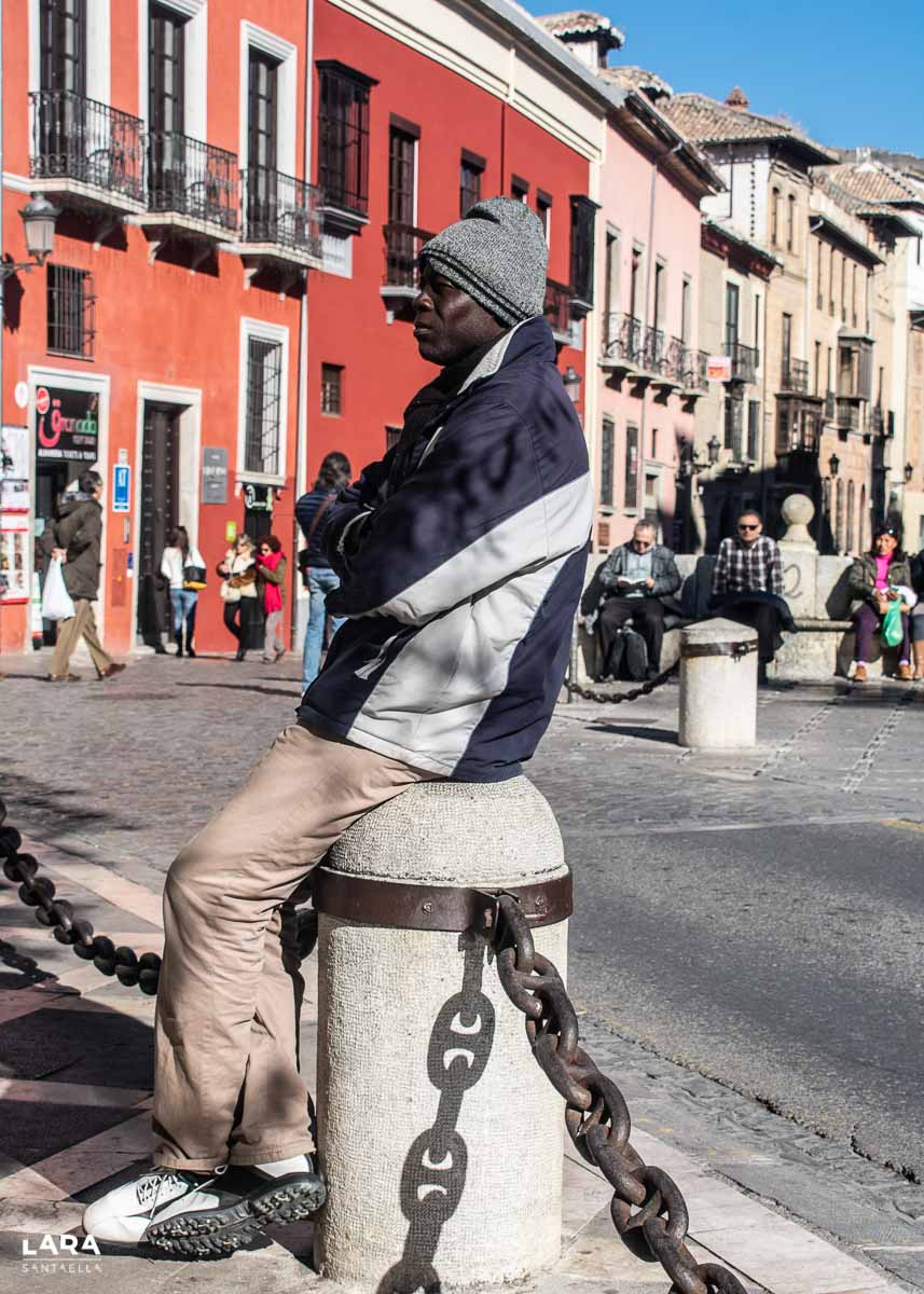 Vendedor ambulante sentado en columna