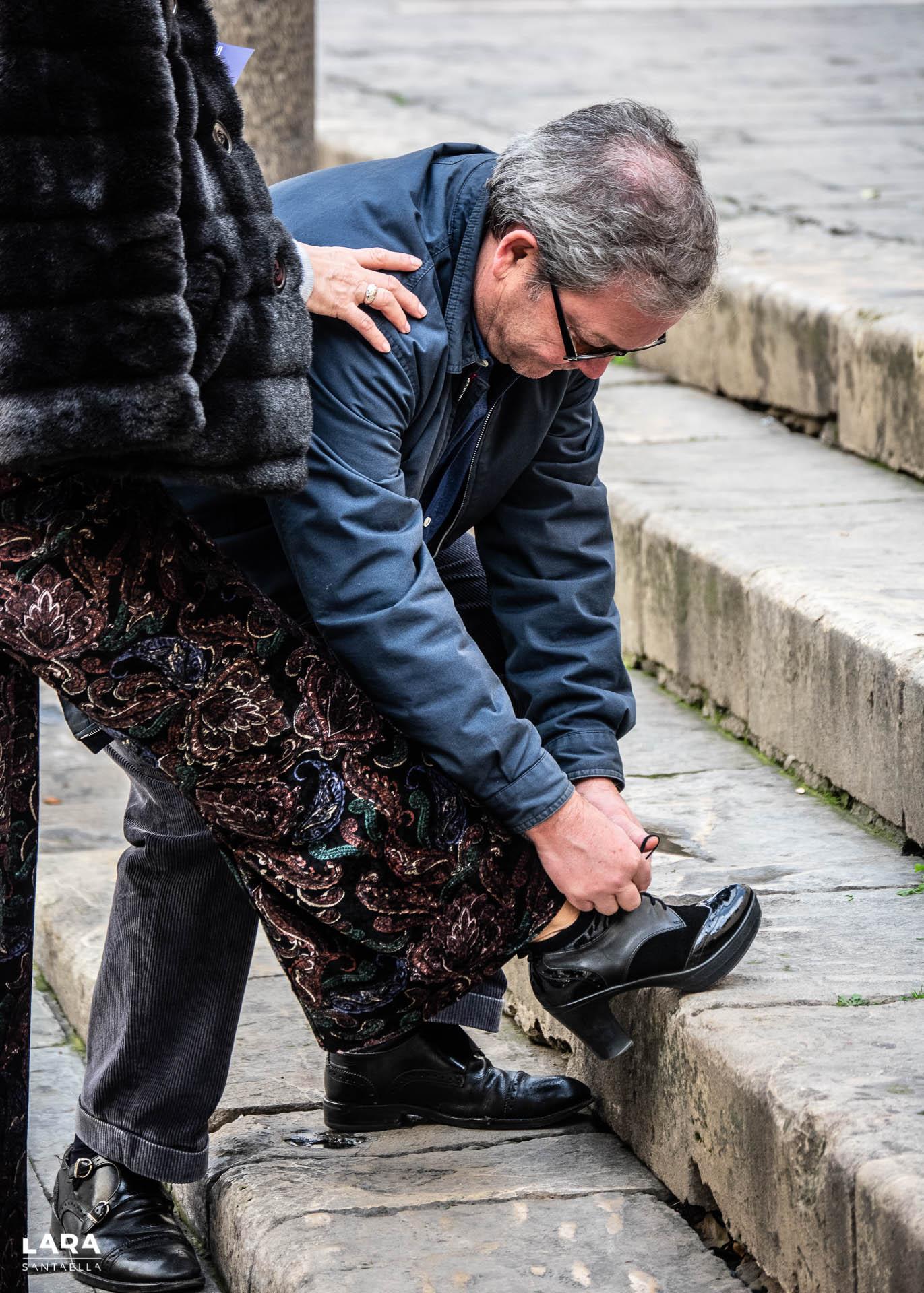 Hombre atando cordones a su mujer