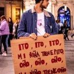 """Un muchacho lleva una pancarta con el lema """"ito ito ito, mi niña tiene pito, oño, oño oño, mi niño tiene coño"""""""